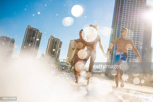 friends running into the sea - gold coast queensland stock pictures, royalty-free photos & images