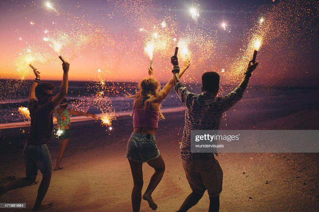 Rearview of friends running together on a beach holding sparkling fireworks