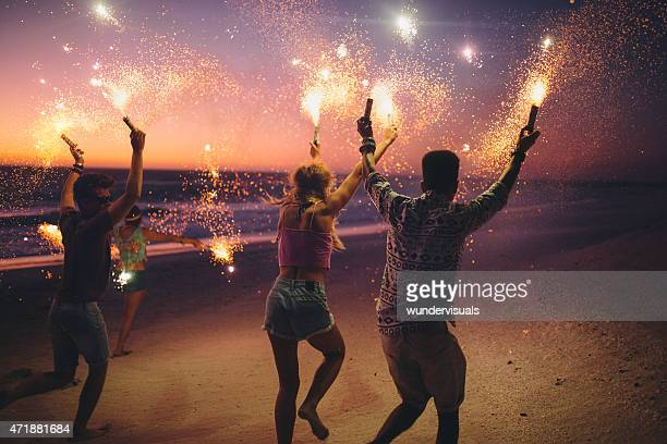 friends running on a beach with fireworks - fireworks stock pictures, royalty-free photos & images