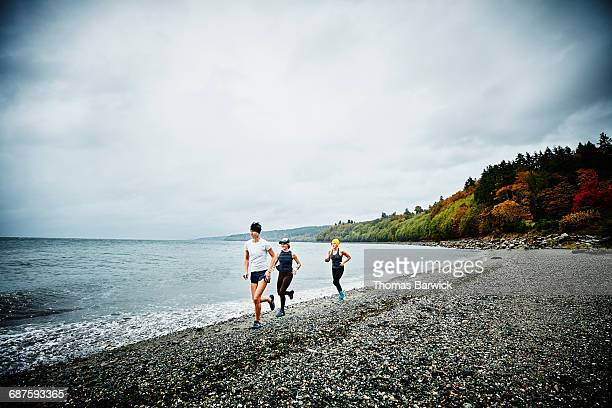 Friends running on beach on stormy afternoon
