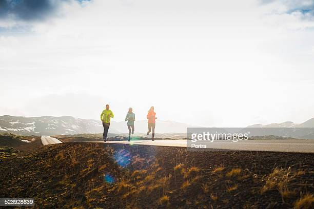 friends running on mountain road against sky - 中距離 ストックフォトと画像