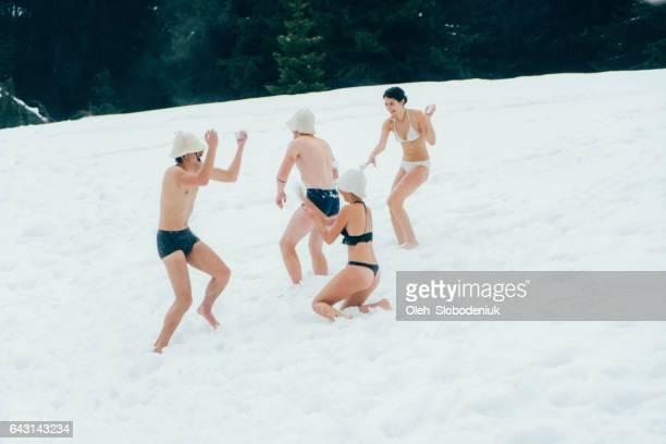 Freunde, die laufen auf Schnee nach dem Waschen in einen Whirlpool im freien