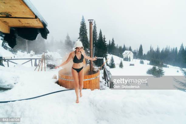 friends running on snow after washing in hot tub outdoors - hot tub stock photos and pictures