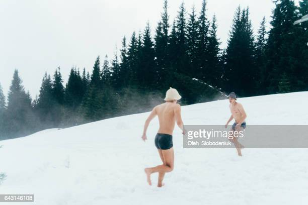 Friends running on snow after washing in hot tub outdoors