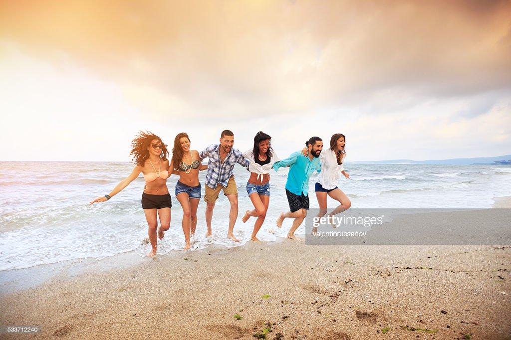 Gli amici correre sulla spiaggia-mano a mano : Foto stock