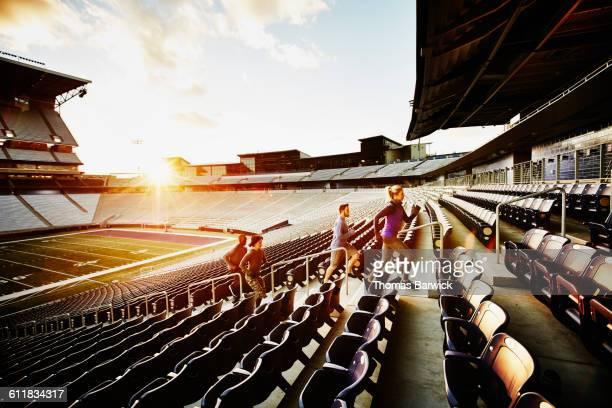 Friends running stairs in empty stadium at sunset