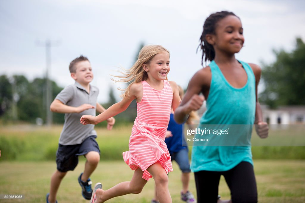 Friends Running Through the Park : Stock Photo