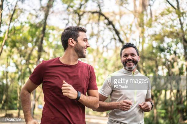 friends running together in a park - only men stock pictures, royalty-free photos & images