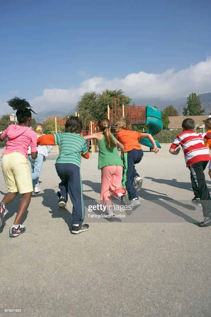 Friends running toward playground : Stock Photo