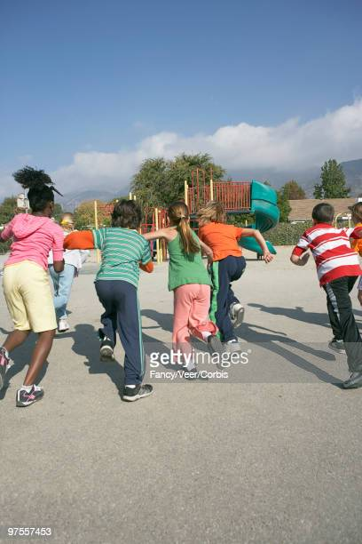 friends running toward playground - climat stock pictures, royalty-free photos & images