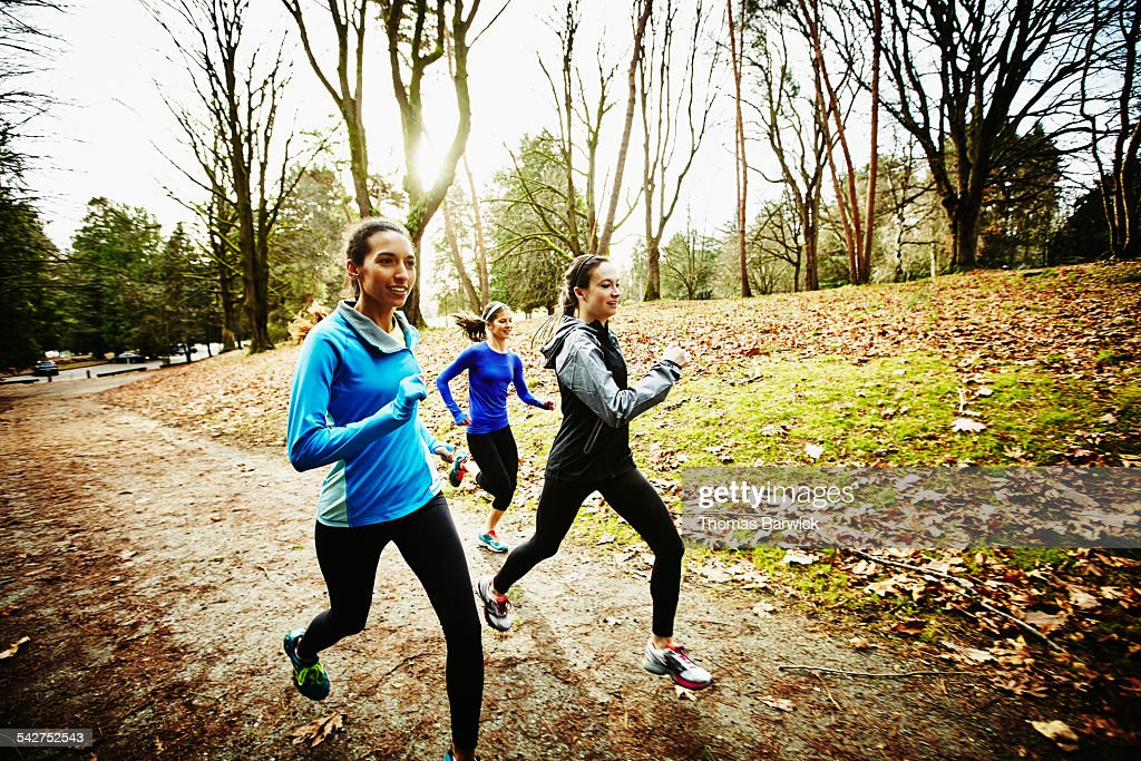 Friends running trails together on winter morning : Stock Photo