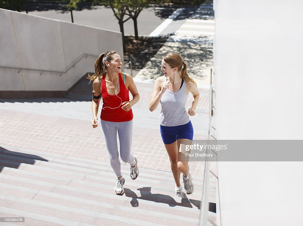 Friends running up urban staircase : Stock Photo