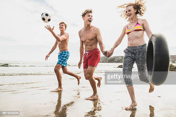 Friends running with a ball and tyre on the beach