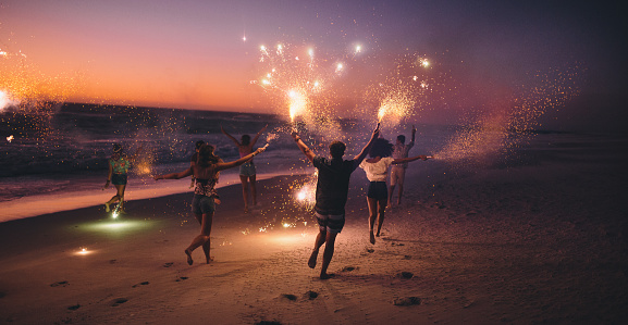 Friends running with fireworks on a beach after sunset - gettyimageskorea