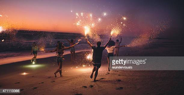 friends running with fireworks on a beach after sunset - beach stockfoto's en -beelden