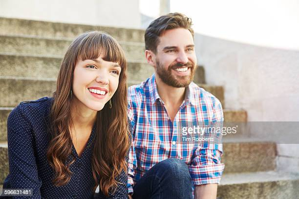 friends sat on steps. - heterosexual couple stock pictures, royalty-free photos & images
