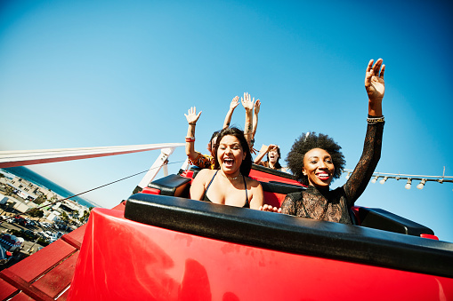 Friends screaming and laughing while riding roller coaster at amusement park - gettyimageskorea