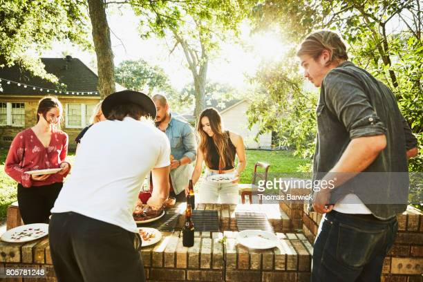 Friends serving barbeque in backyard on summer evening