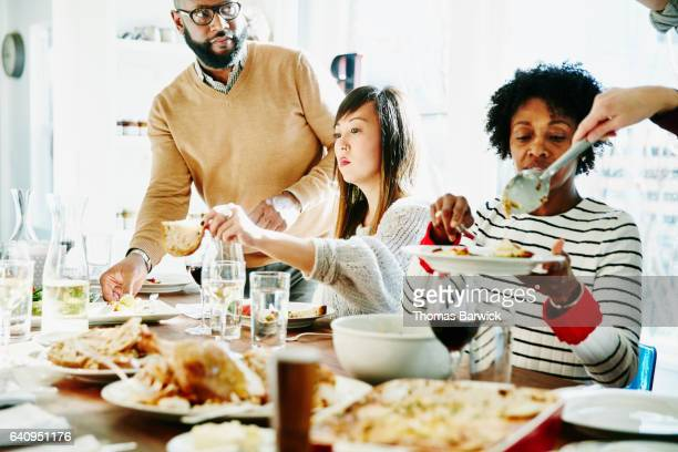 friends serving each other during holiday meal together - first thanksgiving stock photos and pictures