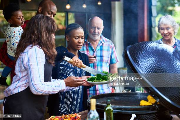 friends serving healthy food from barbecue - celebratory event stock pictures, royalty-free photos & images