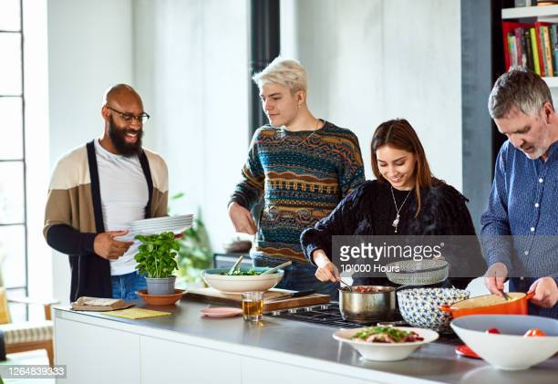 friends serving homemade meal in kitchen - serving food and drinks stock pictures, royalty-free photos & images