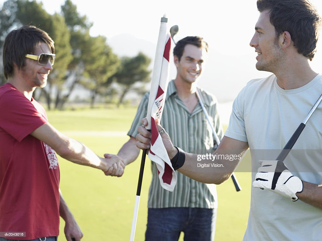 Friends Shaking Hands on a Golf Course : Stock Photo