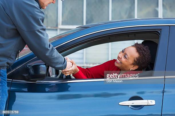 friends shaking hands through car window - roadside stock pictures, royalty-free photos & images
