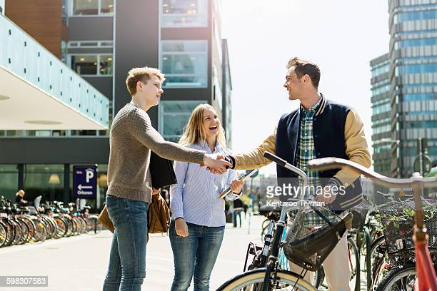 Friends shaking hands while standing by woman at campus