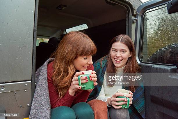 Friends sharing a hot drink in back of car