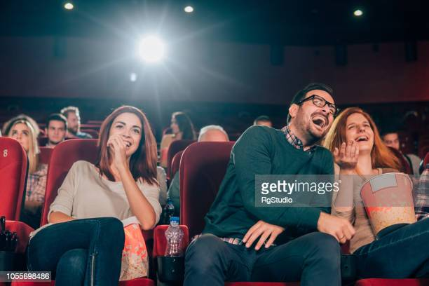 friends sharing a laugh at cinema - film industry stock pictures, royalty-free photos & images