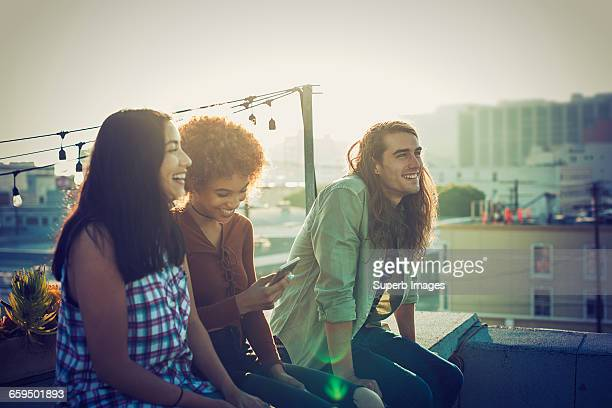 friends sharing a laugh on urban rooftop - 20 29 years stock pictures, royalty-free photos & images
