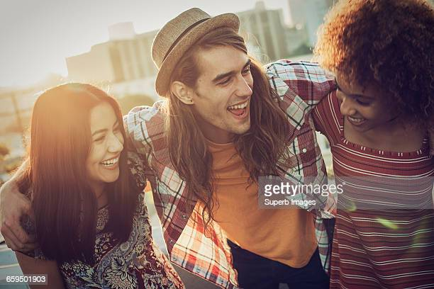 friends sharing a laugh on urban rooftop - close to stock pictures, royalty-free photos & images