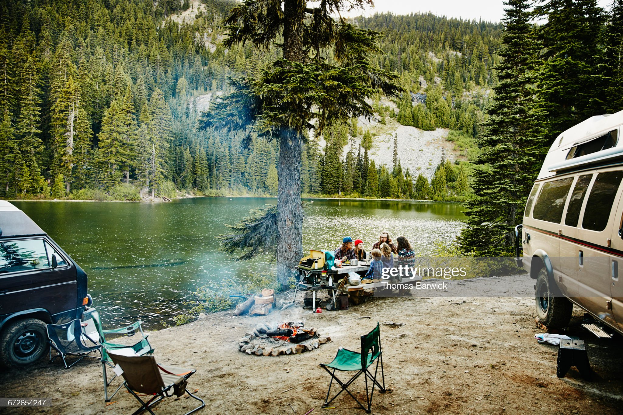 Friends sharing a meal while camping by lake : Stock Photo
