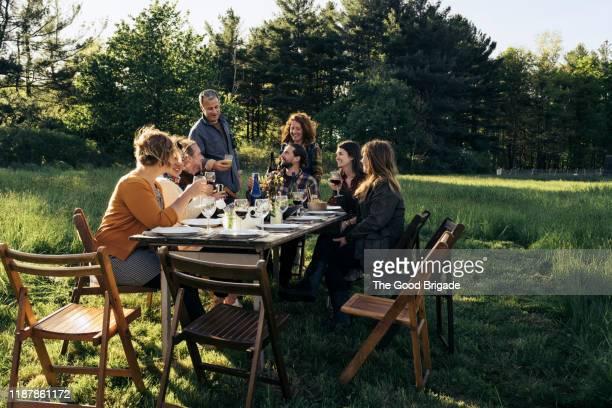 friends sharing a toast at outdoor dinner party - grupo médio de pessoas imagens e fotografias de stock