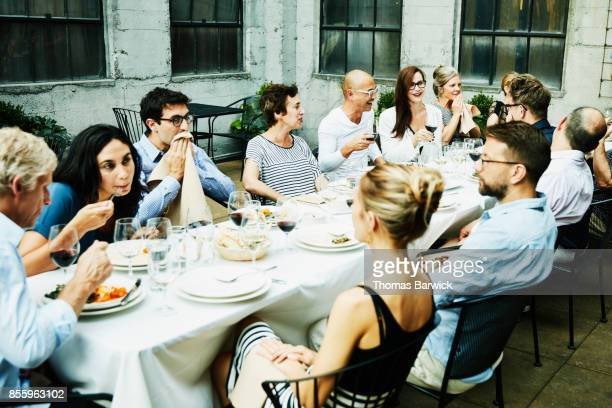 Friends sharing celebration meal on outdoor patio on summer evening