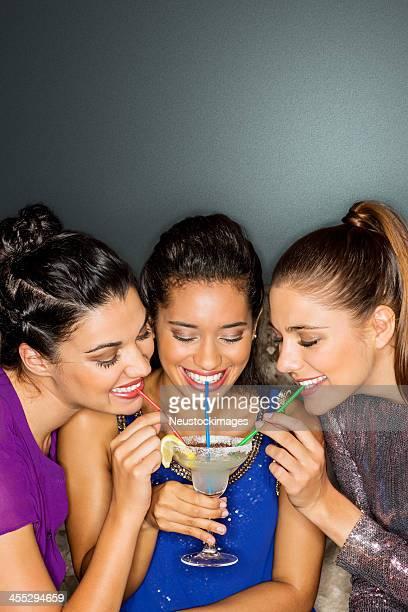 Friends Sharing Cocktail Through Straw In Nightclub