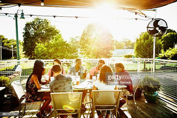 Friends sharing drinks at table on restaurant deck