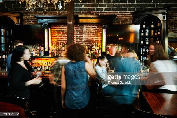 Friends sharing drinks in busy bar motion blur