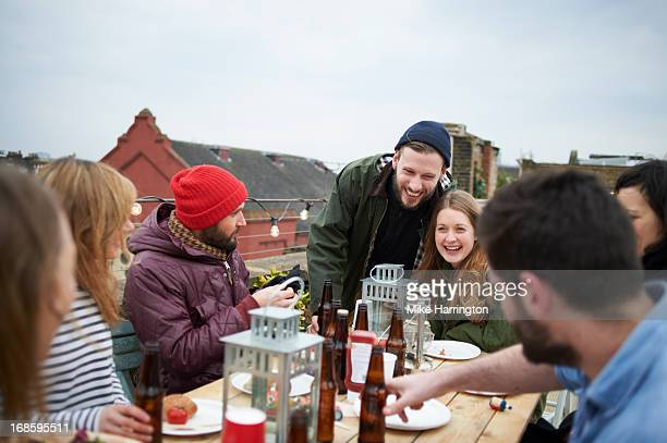 Friends sharing food and drinks in roof garden.