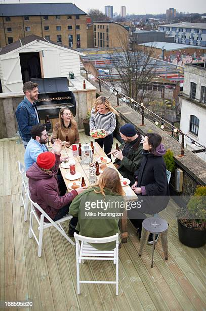 Friends sharing food around table in roof garden.