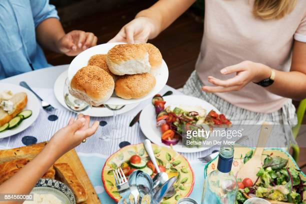 Friends sharing food at dinnerparty, hands passing on plate of bread rolls.