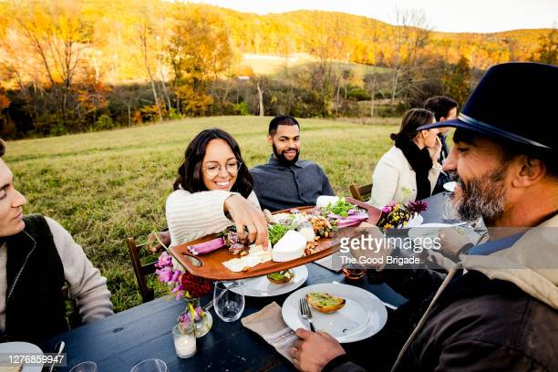 friends sharing food during outdoor dinner party - 様式 ストックフォトと画像