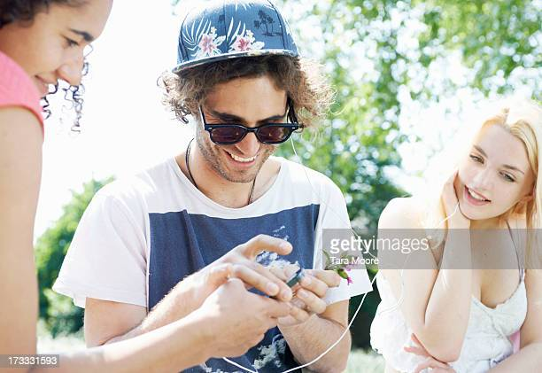 friends sharing headphones and mobile in park