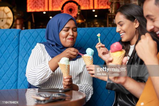 friends sharing ice cream in ice cream parlor - friendship stock pictures, royalty-free photos & images