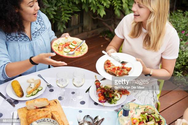 Friends sharing plates of food at dinner party in garden.