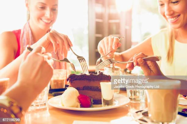 Friends sharing slice of chocolate cake in restaurant