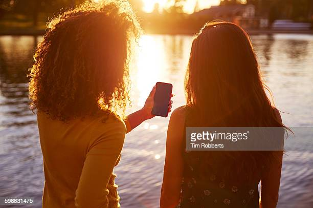 friends sharing smartphone next to river. - twilight stock pictures, royalty-free photos & images