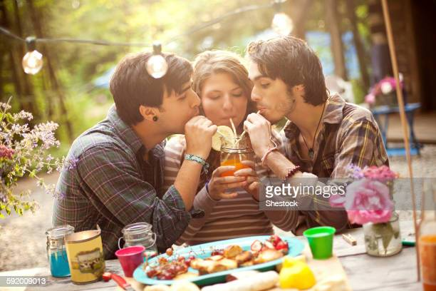 Friends sharing soda at picnic table in forest