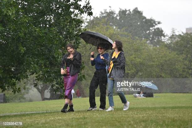 Friends shelter from a sudden downpour of rain on Primrose Hill in London on June 28, 2020.