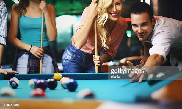 Friends shooting pool.